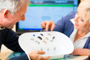 Older man and woman or pensioners with a hearing problem make a hearing test and may need a hearing aid